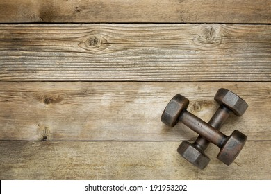 a pair of vintage iron rusty dumbbells on a weathered wood background with a copy space
