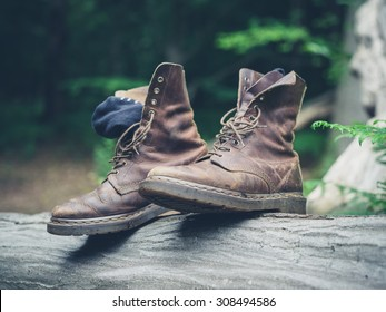 A pair of walking boots on a log in the forest