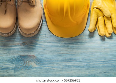 Pair of waterproof boots hard hat leather protective gloves on wooden board construction concept.
