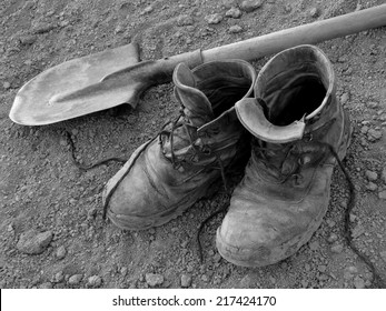 pair of well worn work boots and spade on the ground