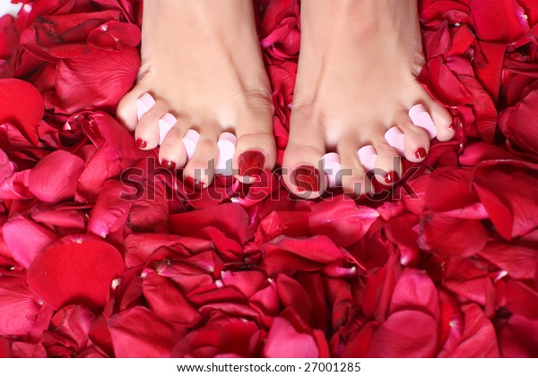 Pair of well-groomed feet against from petals of red roses, please look other photos of this series: