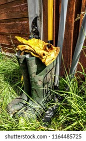 A pair of wellingtons sat outside a shed on the grass with a pair of gloves and gardening equipment behind them.