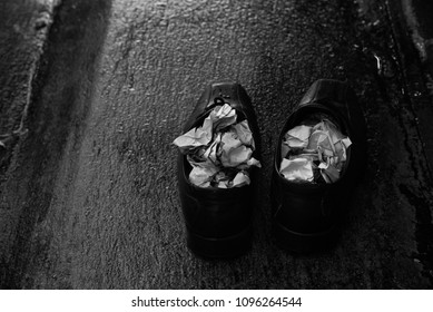 A pair of wet shoes with folded newspaper inside in the rainy day in black and white