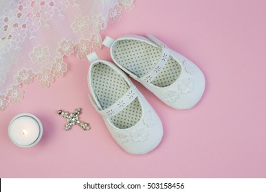 Pair of white baby booties on pink background with lace christening dress and candle