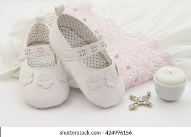 Pair of white baby shoes on embroidered christening white dress, cross and candle