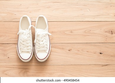A pair of white canvas shoes on a wooden