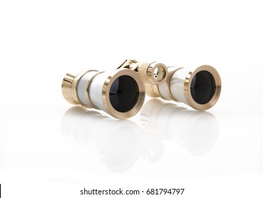 A Pair of White and Gold opera glasses on a white background with refection