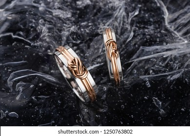 Pair of white gold wedding rings with pink gold knot on black water background. Conceptual silver and gold wedding fashion jewelry. Advertising photo for jeweler