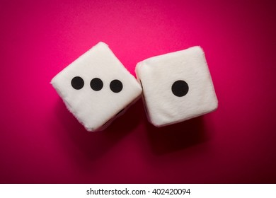 Pair of white plush dices on the pink background