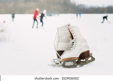 A pair of white retro ice skates on the snow. A pair of female ice skates lying on the snow with skaters in the background.