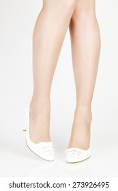 a pair of white shoes with beautiful legs on a white background. close-up