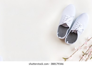 Pair of white sneakers with cherry branches on white background