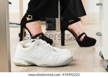 9958ab4cdf7d Pair Of A White Sport Shoes Besides Businesswoman s Foot Wearing High Heels