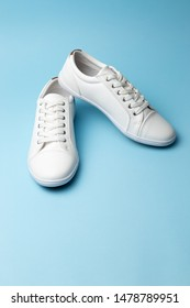 Pair of white trendy sneakers on light blue background. Place for text. Fashion blog or magazine concept.