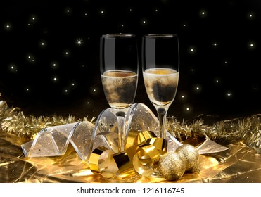 Pair of white wine glass with party ornament over black background. Party and celebration concept