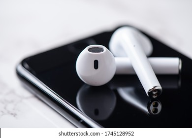 Pair of white wireless earbuds for smartphone. Relaxation concept.