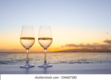 Pair of wine glasses on the beach.