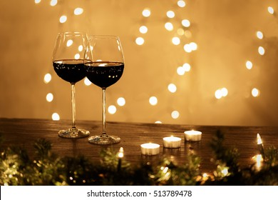 Pair of wine glasses on table with small candles and Christmas lights on background with copy space