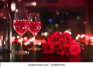Pair of wine glasses red roses in a hotel room. Valentines gift, love, date night concept.