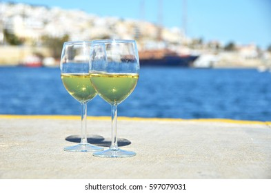 Pair of wineglasses against yachts in Bay of Zea, Attica, Greece