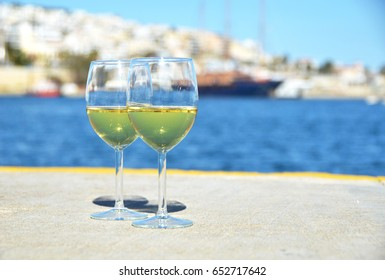 Pair of wineglasses against yachts in Piraeus, Greece