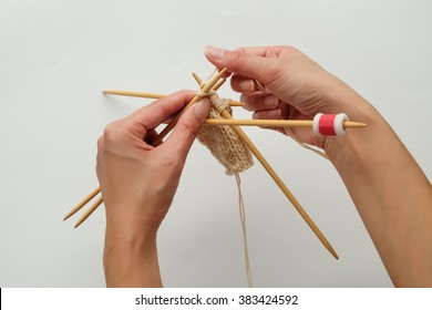 Pair of woman's hands and knitting needles isolated