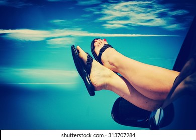 pair of womans legs outside of a car window with the sky in the background with a tone faded instagram filter with a shallow depth of field