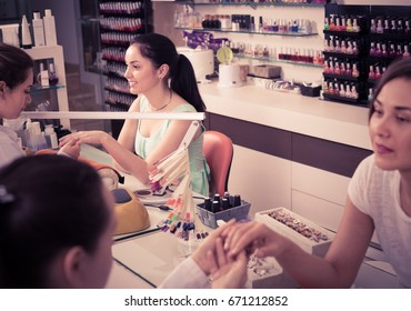pair of women clients getting manicure in modern nail salon