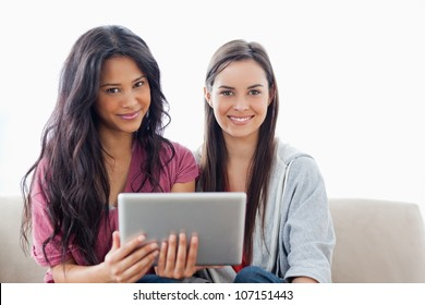 A pair of women looking at the camera as one woman holds a tablet pc