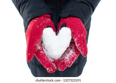 A pair of women's hands wearing bright red gloves and holding a heart made of snow; her black coat can be seen in the background, set against the white snow
