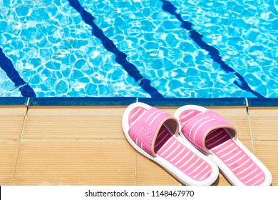A pair of womens plastic sandals by side of swimming pool