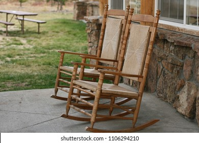 A pair of wooden rocking chairs on the front porch, slightly off center with each other for a natural set up, slightly blurred backyard and stone siding as background