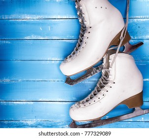 a pair of worn white leather skates for figure skating on a blue wooden background, empty space on the left