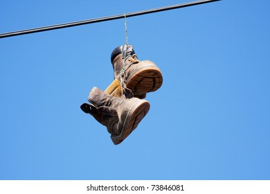 Pair of worn-out old boots slung over a power line against blue sky