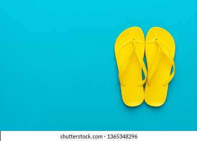 pair of yellow beach flip-flops on the blue background summer concept. minimalist flat lay photo of beach flip-flops with some copy space