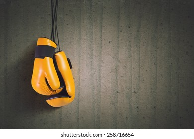 Pair of yellow boxing gloves hanging on all