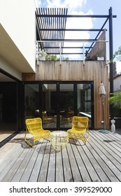 Pair of yellow cane outdoor chairs on wooden deck in contemporary courtyard