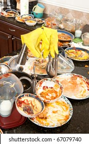A pair of yellow dish washing gloves hangs on a sink faucet surrounded by filthy dishes.