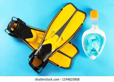 Pair of yellow flippers and diving mask on color background, top view