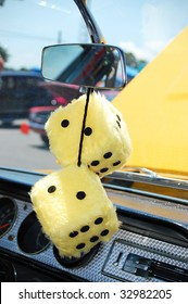 Pair of Yellow Fuzzy Dice Hanging from Mirror