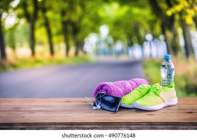 Pair of yellow green sport shoes towel water smart pone and headphones on wooden board. In the background forest or park trail. Accessories for running sport.