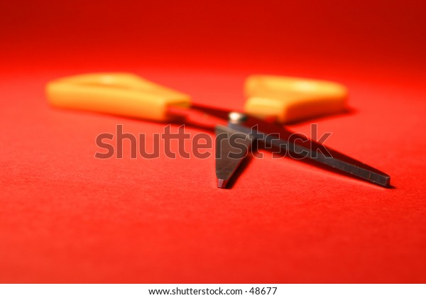 A pair of yellow handled scissors on a red background.
