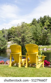 a pair of Yellow Muskoka chairs overlooking the lake at the park in Baysville Ontario