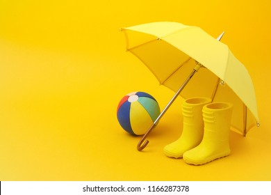 A pair of yellow rain boots and a umbrella and ball on a yellow