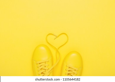 Pair of yellow shoes with heart made of shoelaces on yellow background. Trendy summer color, monochrome image.