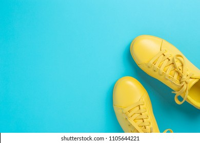 Pair of yellow shoes on blue background. Trendy summer color.