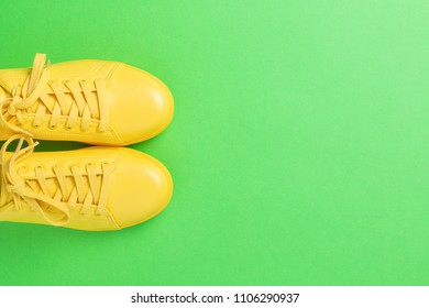 Pair of yellow shoes on green background. Trendy summer color.
