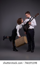 Pair of yong man and woman posing with guitar and suitcase