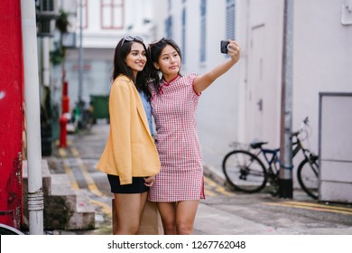 A pair of young Asian girls take a selfie together in an alley during the day. They are a diverse pair of friends, one Chinese in a qipao and the other Indian in a retro outfit. They are both smiling.