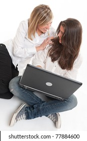 A pair of young laughing female friends using a laptop